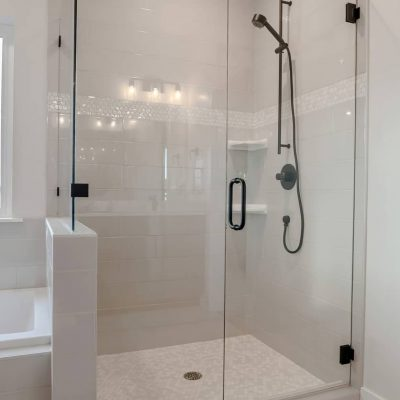 Bathroom shower stall with half glass enclosure adjacent to built in bathtub. The window offers a scenic view of snowy winter landscape and cloudy sky.